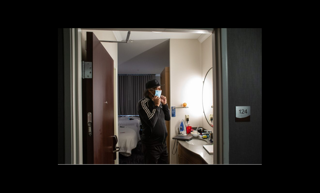 Individual in hotel putting mask on