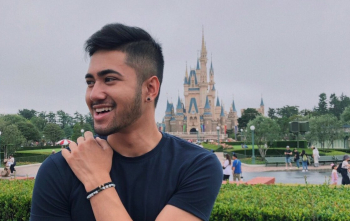 Photo of Andre Menchavez outside with a castle behind him