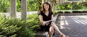 Samantha Fredman seated on a bench outside.